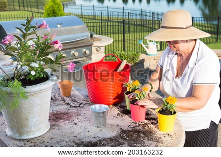 Active senior woman, wearing straw hat and summer casual clothes, while potting ornamental yellow small flowers, as a recreational activity, outdoors, in the garden, at the edge of a lake - stock photo