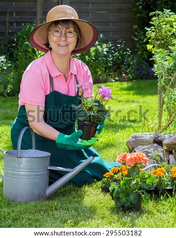 Active senior women working in her garden kneeling on the lush green grass transplanting spring flowers into the flowerbed looking up at the camera with a warm friendly smile - stock photo