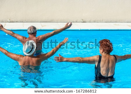 Active seniors getting a workout at the swimming pool - stock photo