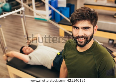 Active slim man is lying and doing sit-ups in gym while  his male instructor is looking at the photographer . - stock photo