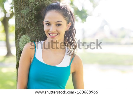 Active smiling brunette looking at camera in a park on a sunny day