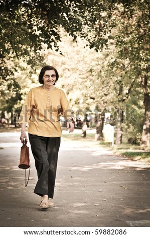 "Active smiling ""80 something"" senior woman walking in park on sunny day - stock photo"