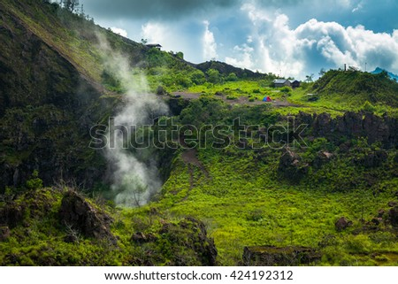 Active smoke Indonesian volcano Batur in the tropical island Bali / Indonesia