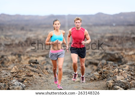 Active sport people runners on rocky trail running path outdoors training for marathon or triathlon. Fit young fitness model man and asian woman training together outside on Big Island, Hawaii, USA. - stock photo