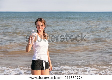 Active sport woman drinking water after exercising at the beach. Caucasian girl fitness model is at coast. Female athlete after work out in sunny light. Weight loss. Healthy lifestyle. Copy space.