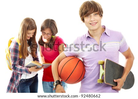 Active teenager with skateboard and ball looking at camera - stock photo