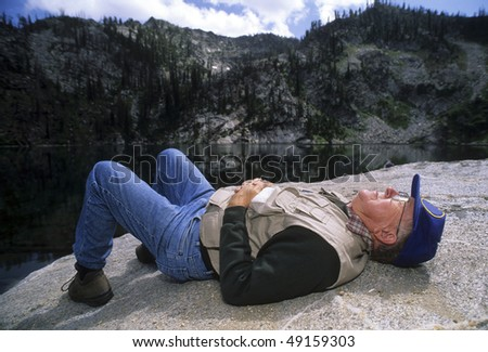 Active tired senior man sleeping, napping on a rock on a hike. - stock photo