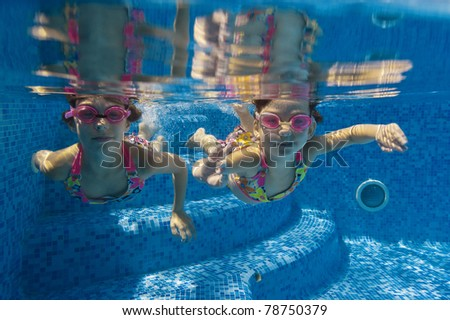 Active underwater kids in swimming pool. Girls swim and having fun. Child sport on summer vacation