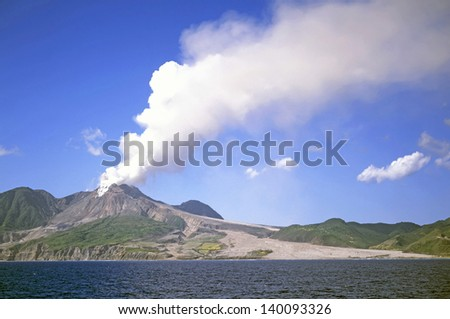 Active volcano in the Soufriere Hills Montserrat Lesser Antilles Leeward Islands West Indies Caribbean with solidified lava fields down to sea - stock photo