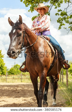 Active western cowgirl woman in hat training riding horse. Equestrian sport competition and activity. - stock photo