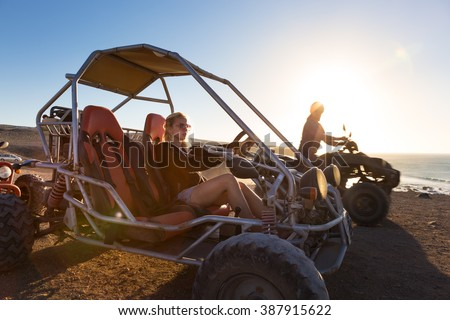 Active woman driving quadbike on dirt road by the sea in sunset. - stock photo