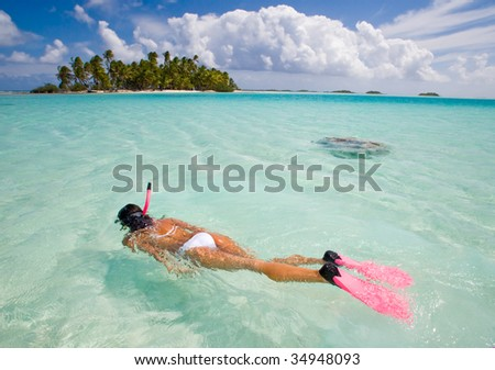 active woman free diving snorkeling in beautiful blue ocean on summer vacation
