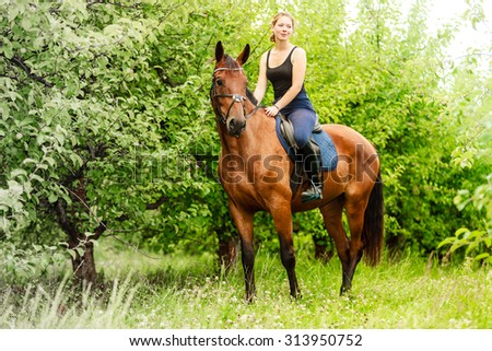 Active woman girl jockey training riding horse. Equitation sport competition and activity. - stock photo