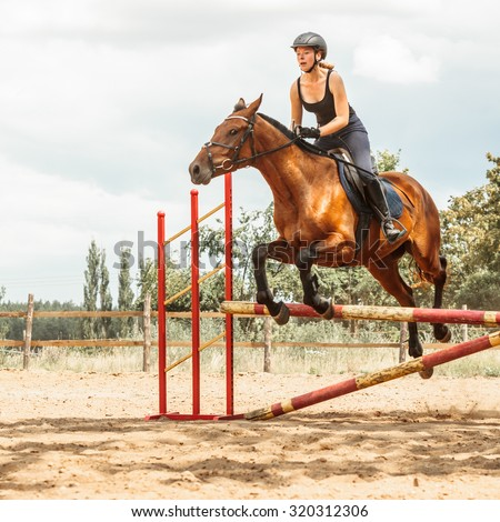 Active woman girl jockey training riding horse jumping over fence. Equestrian sport competition and activity. - stock photo