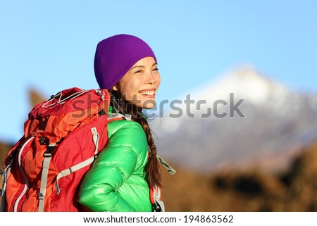 Active woman hiker living healthy lifestyle hiking outdoors wearing backpack smiling happy. Beautiful female trekking with looking with aspirations. Mixed race Asian Caucasian girl in her 20s. - stock photo