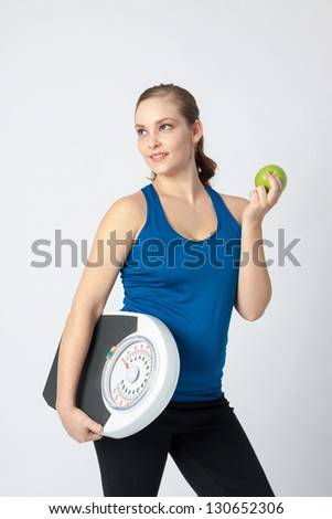 Active woman  holding an apple and scale. Concept of image is healthy diet.