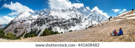 Active woman in snowy Caucasus mountains, cute girl sitting on the hill, spring vacation concept - stock photo
