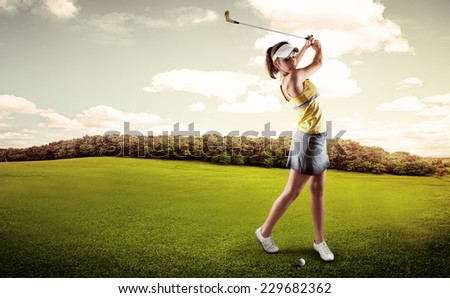 Active woman player hitting the ball on golf court. Sporty female exercising golf play on nature over beautiful landscape background.  - stock photo