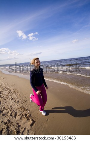 Active woman running on the beach