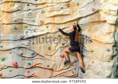 active young business woman on rock wall in sport center - stock photo