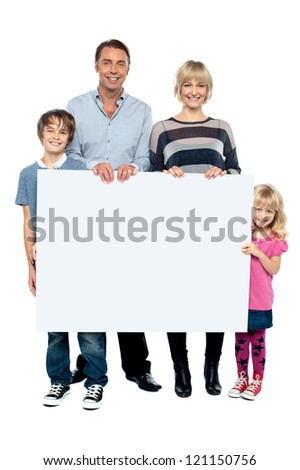 Active young family displaying a blank ad board to the camera. Full length portrait - stock photo