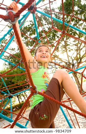 Active young girl climbing the spider web playground activity in summer. - stock photo