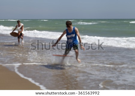 active young guys ride on  skimboard