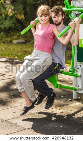 Active young man and woman exercising on pulldown machine. Muscular strong guy and girl in training suit working out at outdoor gym. Sport fitness and healthy lifestyle concept.