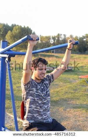 Active young man exercising on chest press machine outdoor at sunset