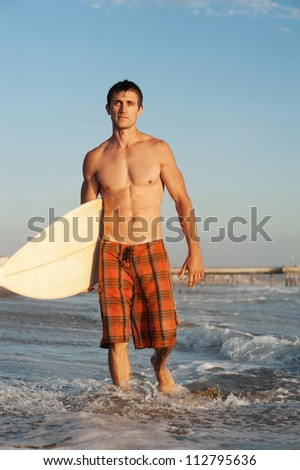 active young surfer holding a surfboard at the beach - stock photo