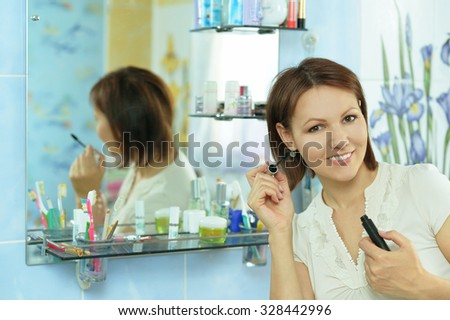 active young woman doing make up in the bathroom