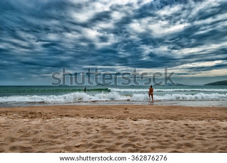 Active young woman jumping into water in summer colorful image  Image of Brazilian beach in tropical paradise Buzios with people in the sea under a dramatic blue sunset sky with clouds. - stock photo