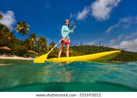 Active young woman on tropical beach vacation paddling on stand up board - stock photo