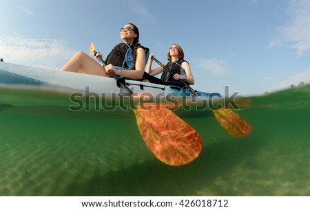 Active young women smiling while kayaking in ocean - stock photo