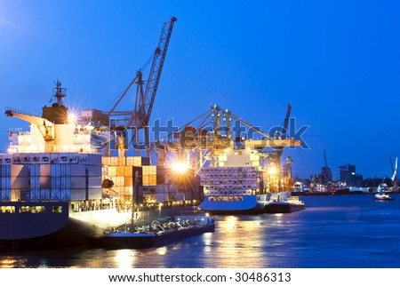 Activity of loading and unloading of huge container ships in a commercial harbor, with a city skyline in the background at dusk - stock photo