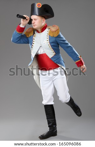 Actor dressed as Napoleon. Historical costume. Napoleon looks through a spyglass. - stock photo