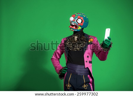 Actor in  pink suit and mask zombie holding  phone. - stock photo