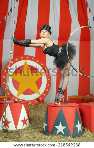 Actress in black tutu and top hat stands on pedestal and stretches to ladder - stock photo