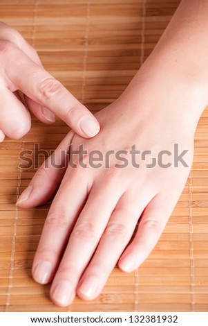 Acupressure, acupuncture point Hegu, LI4. Photo shows how to find this point. - stock photo