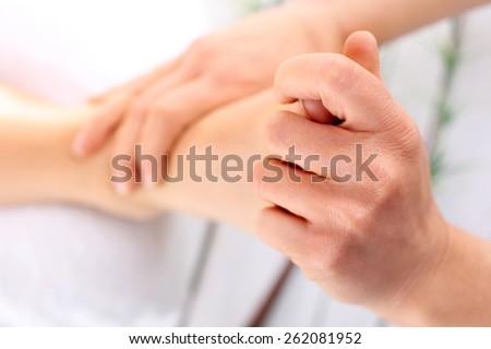 Acupressure, foot massage.Masseuse massaging woman's foot. - stock photo