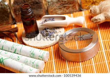 Acupuncture needles, moxa sticks, lavender petals with macerated oil, giner and herbs in jars. TCM Traditional Chinese Medicine concept photo - stock photo