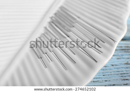 Acupuncture needles on plate on wooden table, closeup - stock photo