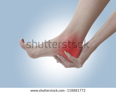Acute pain in a woman ankle. Female holding hand to spot of ankle-ache. Concept photo with Color Enhanced blue skin with read spot indicating location of the pain. Isolation on a white background.
