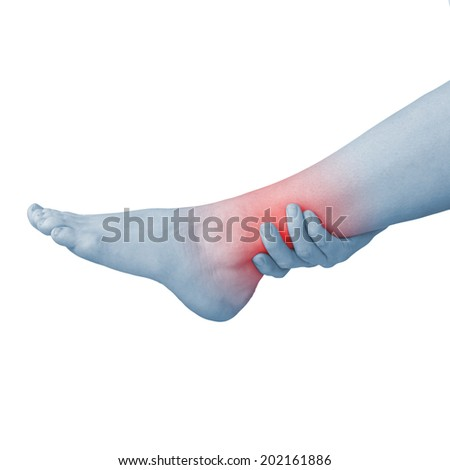 Acute pain in a woman ankle. Woman holding hand to spot of ankle-aches. - stock photo