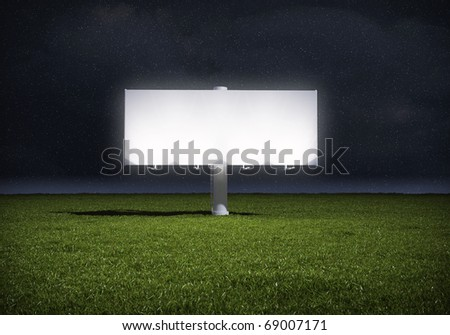 Ad billboard standing in a field of grass - night version - stock photo