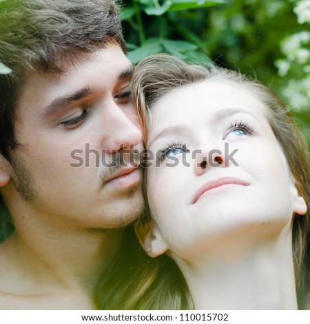 Adam & Eve: Young beautiful happy romantic couple embracing tenderly among green leaves - stock photo