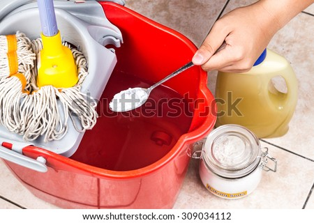 Add baking soda to floor cleaner and water for house cleaning - stock photo