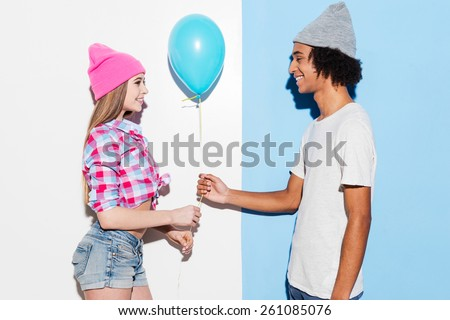 Add some colors. Handsome young African man giving a blue balloon to his girlfriend while standing against colorful background - stock photo