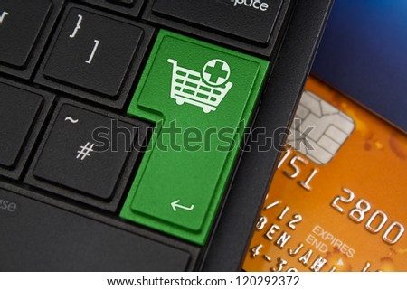 Add to Cart Enter Key on a modern laptop qwerty keyboard with bank smart card underneath to represent on-line shopping - stock photo