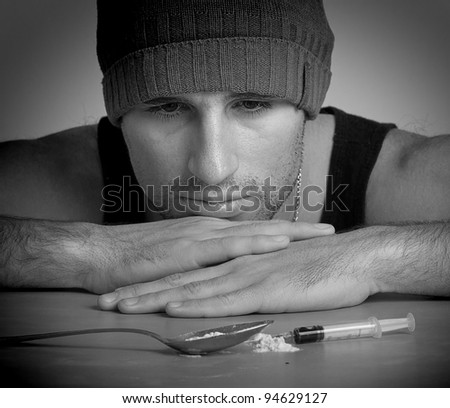 addict, a syringe, the drugs and heroin close up monochrome - stock photo